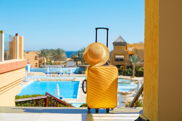 Travel, summer holidays and vacation concept. yellow suitcase with hat on background of hotel pool area in egypt.