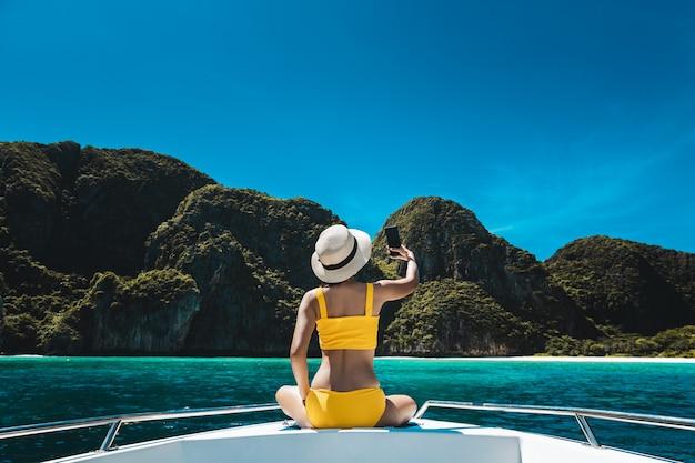 여행 여름 휴가 개념, 비키니와 휴대 전화를 갖춘 행복한 솔로 여행자 아시아 여성은 태국 마야 베이 푸켓에서 보트에서 휴식을 취하고 셀카를 찍습니다.