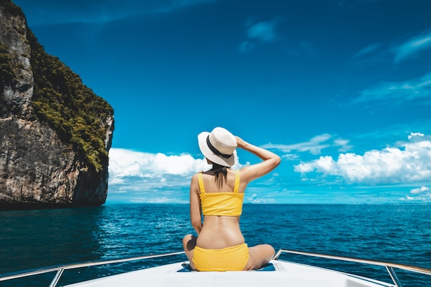 Travel summer vacation concept, happy solo traveler asian woman with bikini and hat relax in boat on sea at phuket thailand