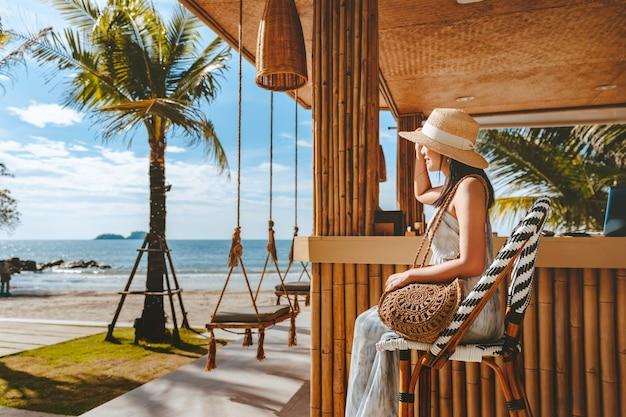 여행 여름 휴가 개념, 모자와 드레스를 입은 행복한 여행자 아시아 여성은 태국 코창 해변 카페에서 그네에서 휴식을 취합니다.