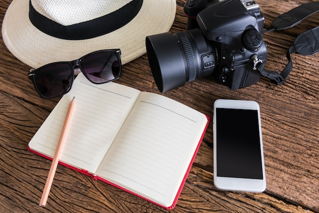 Travel, summer vacation, tourism and objects concept. close up of hat, notebook, pencil, camera, sma