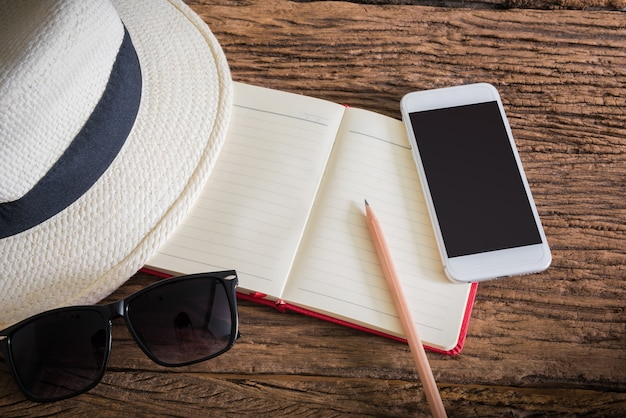 Travel, summer vacation, tourism and objects concept. close up of hat, notebook, pencil, smartphone