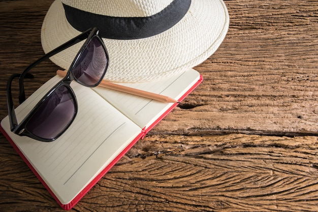 Travel, summer vacation, tourism and objects concept. close up of hat, notebook, pencil and sunglass