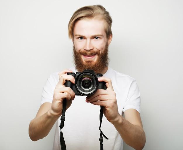 여행, 기술 및 라이프 스타일 개념 : 디지털 카메라로 사진을 찍는 젊은 수염 사진 작가.
