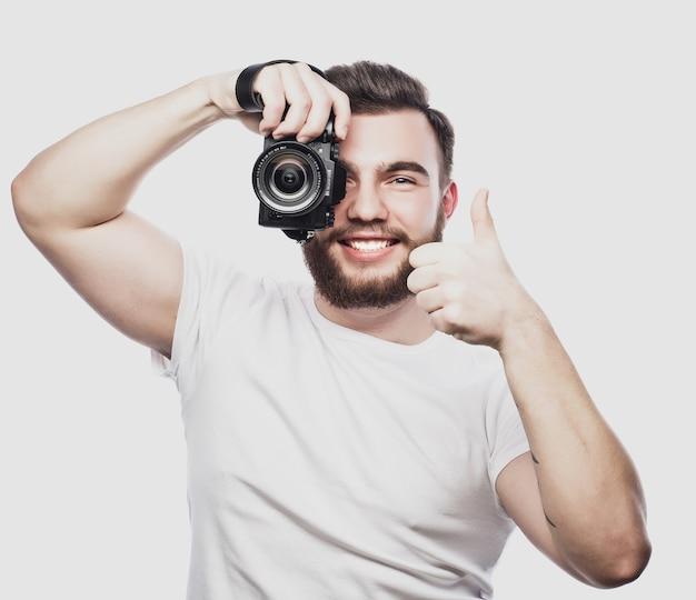 여행, 기술 및 생활 방식 개념: 수염을 기른 젊은 사진가가 디지털 카메라로 사진을 찍고 있습니다.