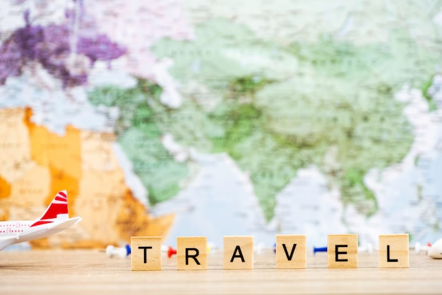 Travel text object and airplane toys on the wooden table. world map in background.