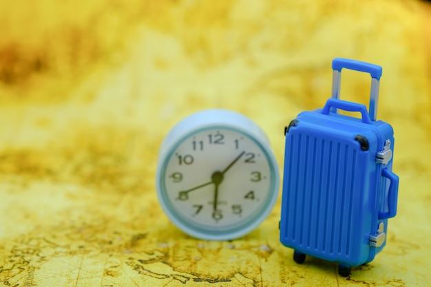 Travel and time concept. close up of mini toy blue baggage with round clock on world map.