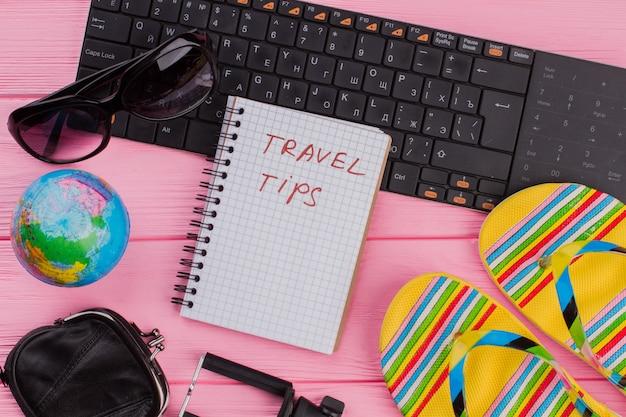 ピンクのテーブルトップの背景に女性の旅行者用アクセサリーメガネ財布とビーチサンダルを備えたノートブックの旅行のヒント。グローブと黒のキーボード。
