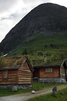 노르웨이로 여행하면 산기슭에 풀로 자란 지붕이있는 집들이 있습니다.