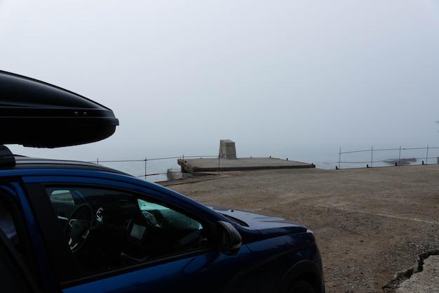 Поездка к морю на машине. кроссовер с багажником стоит на фоне моря.
