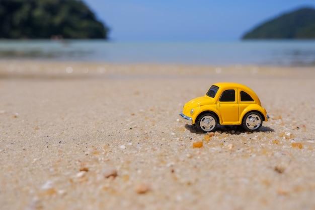 Путешествие к морю, маленькая желтая машина на пляже. концепция отдыха и туризма. открытка с маленькими