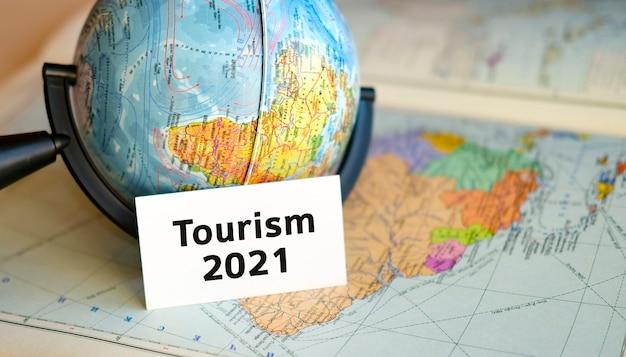 Путешествие туризм 2021 текст на белом листе на земном шаре на синей карте атласа