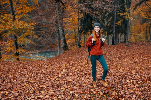 Путешествие, туризм и молодая женщина с рюкзаком гуляет в парке в природе, пейзаж высокие деревья, опавшие листья, река. фото высокого качества