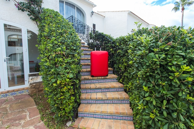 旅行、観光、アクセサリーのコンセプト-自然の表面の階段に立っている赤いスーツケース。