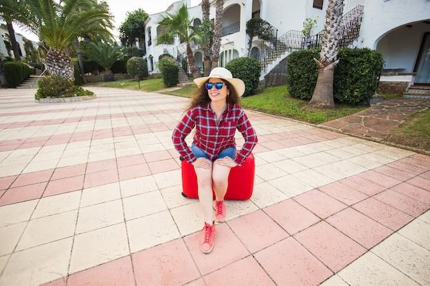 旅行、観光、休日のコンセプト-メガネと帽子の赤いスーツケースに座って笑顔で幸せな若い女性。