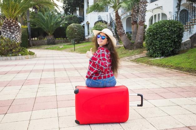 旅行、観光、休日のコンセプト-眼鏡と帽子の赤いスーツケースに座って親指を立てて笑っている幸せな若い女性。