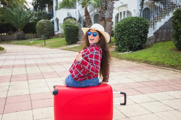 旅行観光と休日のコンセプトメガネと帽子の赤いスーツケースに座って幸せな若い女性