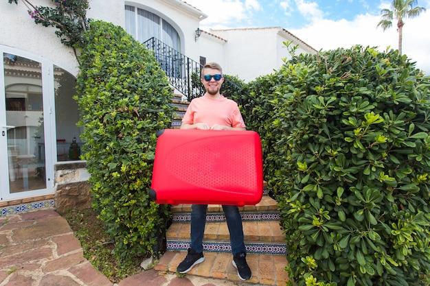 旅行、観光、人々の概念。赤いスーツケースを手に階段に立って笑っている若い男。