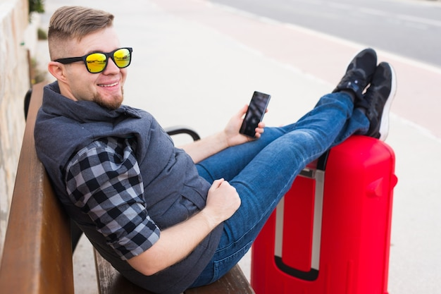 Концепция путешествий, туризма и людей - красивый мужчина сидит и кладет ноги на чемодан, смотря что-то в своем мобильном телефоне.