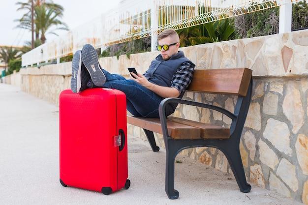 旅行、観光、人々の概念。ハンサムな男が座ってスーツケースに足を置き、携帯電話で何かを見ています。