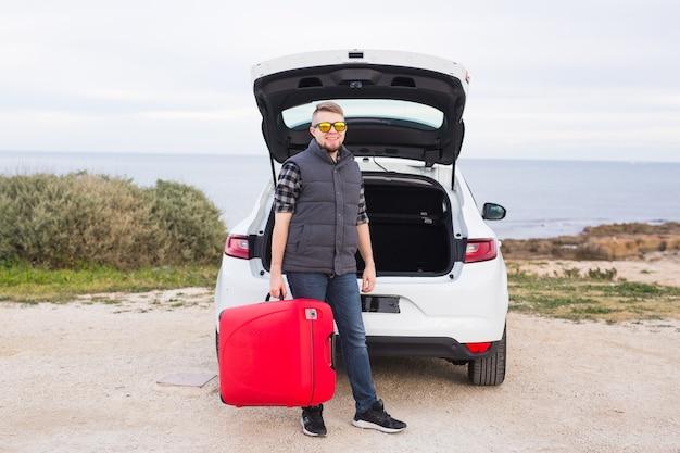 旅行、観光、人々の概念。赤いスーツケースと立っている眼鏡の幸せな男