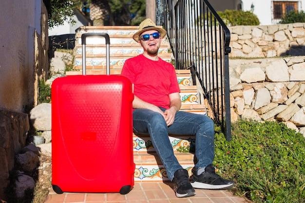 旅行、観光、人々の概念-赤いスーツケースと帽子をかぶって階段に座っている幸せな男。