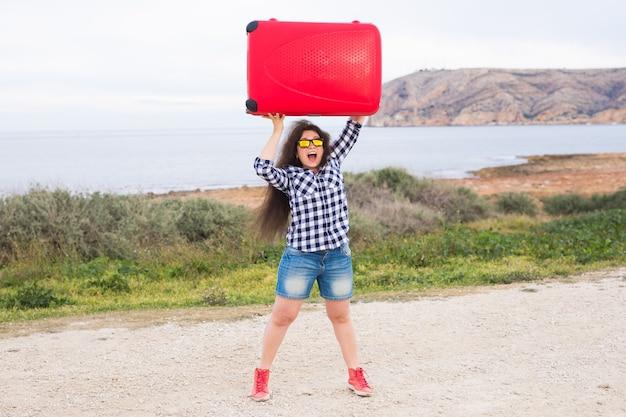 여행, 관광 및 사람 개념입니다. 큰 빨간 가방을 머리 위로 들고 재미있는 안경을 쓰고 자연 배경에서 웃고 있는 행복한 여자.