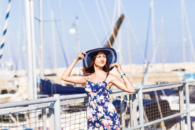 旅行観光と人々の概念。マリーナでボートの近くに立っている帽子を持つ若い女
