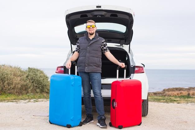 Концепция путешествий, туризма и поездки - молодой человек сидит в открытом багажнике автомобиля с двумя чемоданами и улыбается.