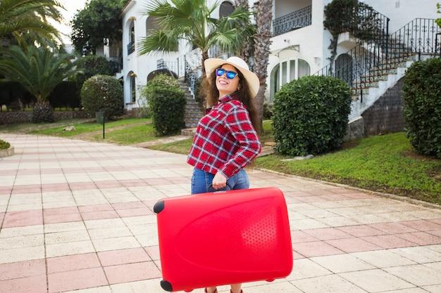 旅行、観光、休暇のコンセプト-赤いスーツケースと笑顔で旅行に行く若い女性。