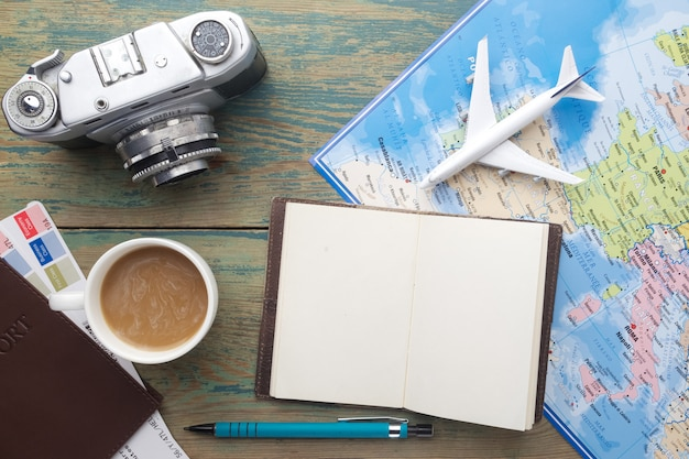 Travel, tourism - close up note book, vintage camera, toy airplane and touristic map on wooden table.
