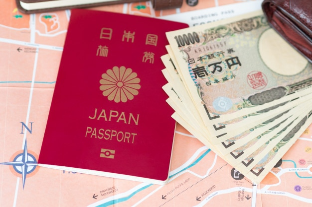 Travel or tourism concept. japanese passport and banknotes on map