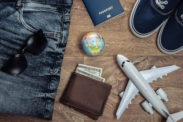 Travel or tourism concept. jeans, purse with hundred dollar bills, sneakers, smartphone, passport, sunglasses, airplane, globe on wooden floor. top view. flat lay
