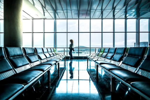 一人の孤独な立っている女性が空港のゲートで飛行を待ち、他の誰もいないコロナウイルス封鎖制限の概念のための旅行観光危機の緊急事態