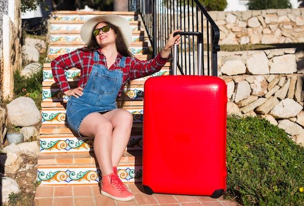 旅行、観光、感情、人々のコンセプト。赤いスーツケースと帽子の階段に座っている幸せな若い女性。