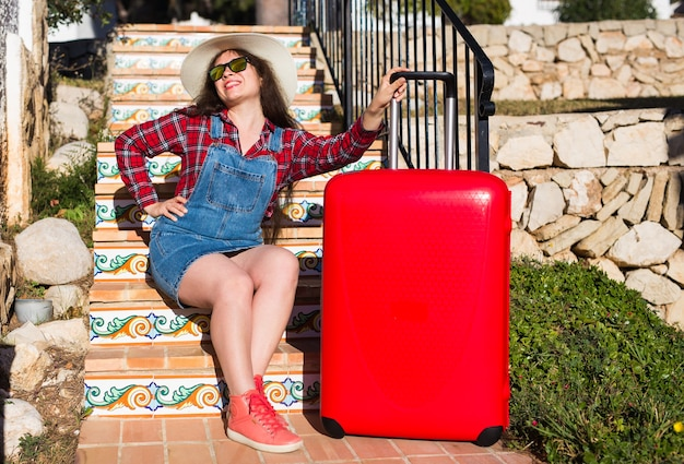 Travel, tourism, emotions and people concept. happy young woman sitting on stairs in a hat with red suitcase.