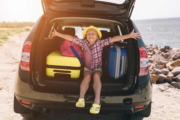 Travel, tourism - girl with bags ready for the travel for summer vacation. child going on adventure. car travel concept