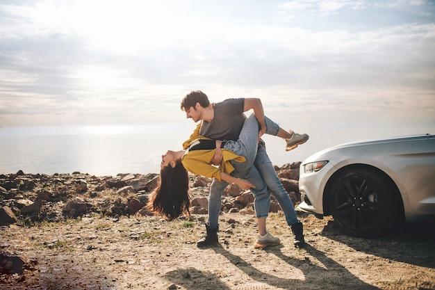 旅行、観光-屋外の車の近くで踊るハンサムなひげを生やした男性と魅力的な若い女性。旅行のコンセプト。ロマンチックなカップルがビーチで車の近くに立っています。マッスルカー。