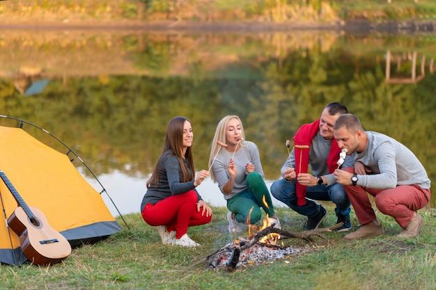 旅行、観光、ハイキング、ピクニック、人々のコンセプト-湖の近くのキャンプファイヤーでソーセージを揚げる幸せな友人のグループ。