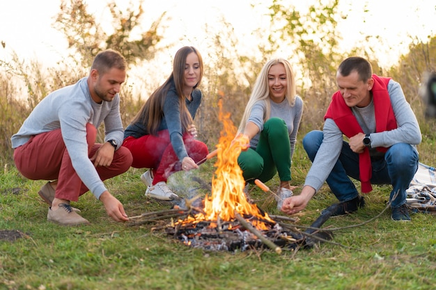 旅行、観光、ハイキング、ピクニック、人々のコンセプト-キャンプファイヤーでソーセージを揚げる幸せな友人のグループ