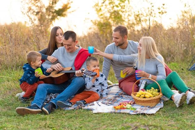 旅行、観光、ハイキング、ピクニック、人々のコンセプト-テントでキャンプとギターを弾く飲み物と幸せな友人のグループ
