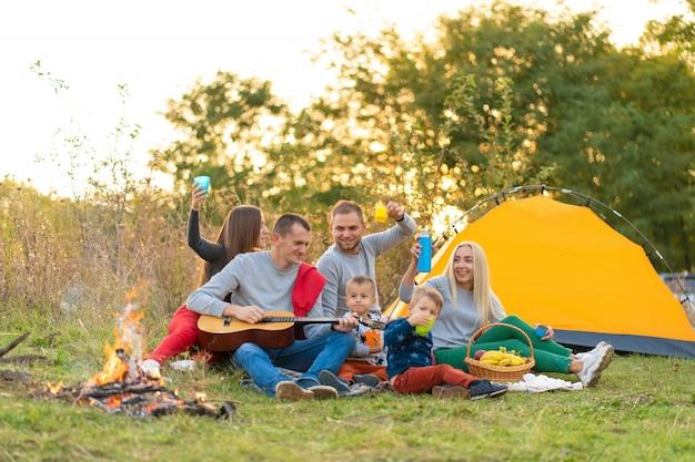 旅行、観光、ハイキング、ピクニック、人々のコンセプト-テントでキャンプとギターを弾く飲み物と幸せな友人のグループ Premium写真