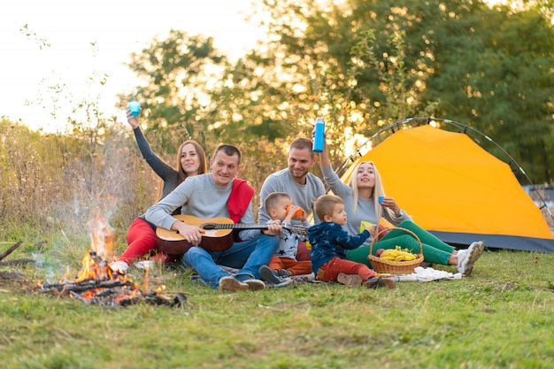 旅行、観光、ハイキング、ピクニック、人々のコンセプト-テントとキャンプでギターを弾く飲み物と幸せな友人のグループ