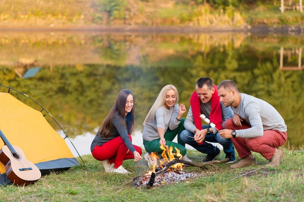 Travel, tourism, hike, picnic and people concept - group of happy friends frying sausages on campfire near lake.