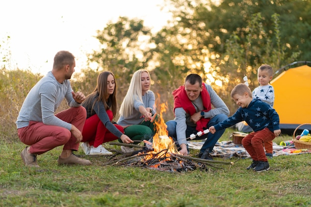 Travel, tourism, hike, picnic and people concept - group of happy friends with kids frying sausages on campfire.