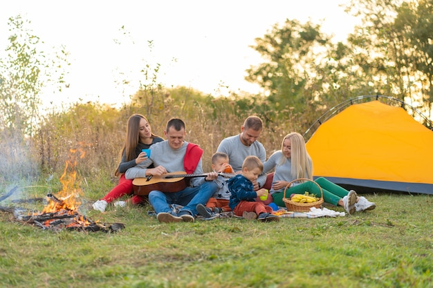 Travel, tourism, hike, picnic and people concept - group of happy friends with tent and drinks playing guitar at camping.