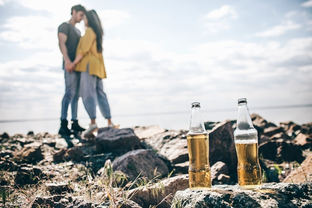 旅行、観光-男性と女性は折りたたみ式のポータブルテーブルで水の近くでシャンパンを飲みます。水の近くのピクニック。冒険に行くカップル。車の旅のコンセプト。