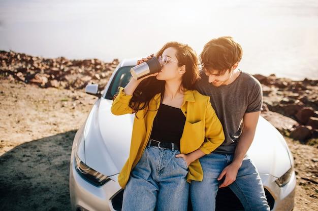 旅行、観光-男性と女性は車の近くでコーヒーやお茶を飲みます。冒険に行くカップル。車の旅のコンセプト。