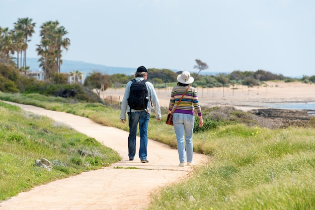 Travel and tourism. mature family couple enjoying view together walking along the seashore, view from the back