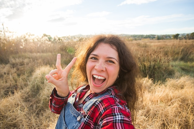 Travel, tourism and nature concept - young woman fooling around taking selfie on field